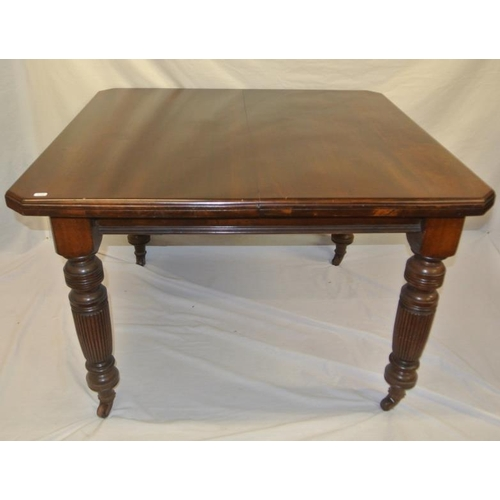 60 - Edwardian mahogany dining table with angled corners, on reeded turned tapering legs with casters...