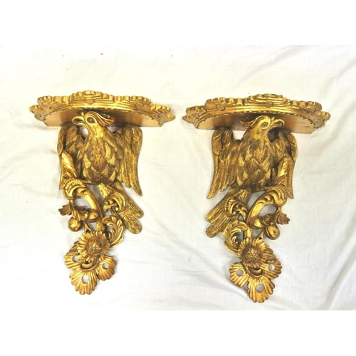 24 - Pair of gilt wall brackets with ornate eagle carving...