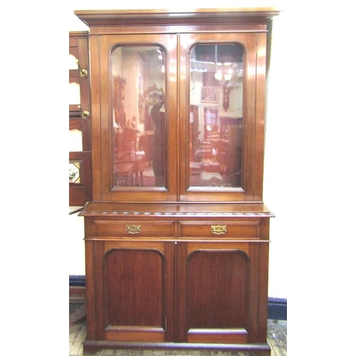 25 - Edwardian mahogany bookcase with glazed doors, shelved interior, two frieze drawers, presses under w...