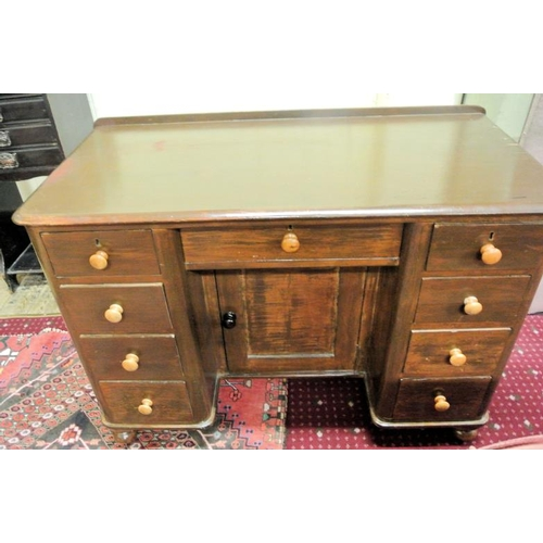 16 - Edwardian kneehole desk with side and central drawers and press, on turned feet...