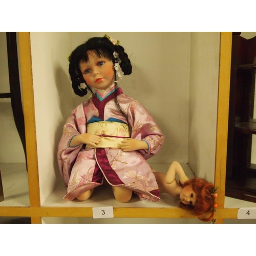 3 - Two porcelain dolls. One large oriental and one small with numbered back...