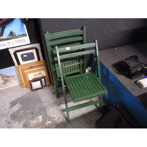 3 - Three green wooden fold out chairs...