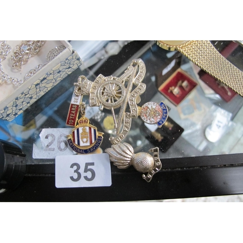 35 - Various pins and cap badge...