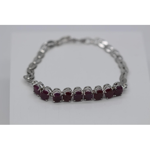 22 - ***£17,775.00*** SILVER LADIES RUBY BRACELET, SET WITH 7.11 CARATS OF OVAL CUT RUBIES, clarity- I1, ...
