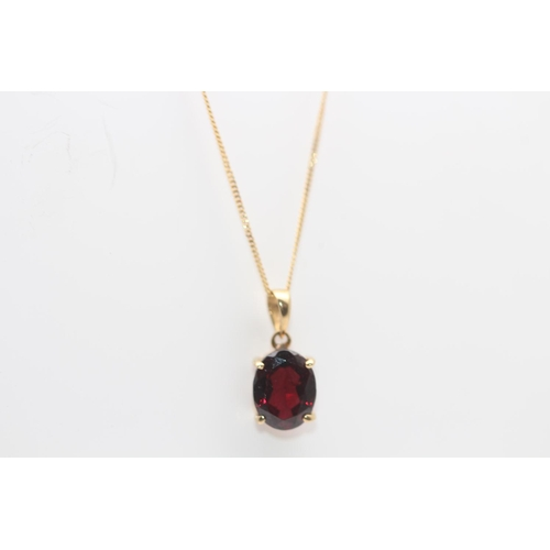 13 - 9CT YELLOW GOLD PENDENT AND NECKLACE, PENDENT IS SET WITH DARK RED STONE...