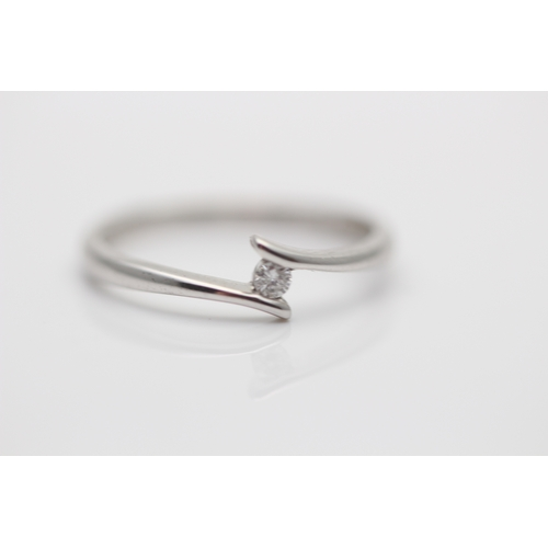 59 - 9CT WHITE GOLD LADIES CROSS OVER RING SET WITH A SINGLE BRILLIANT CUT 0.10 NATURAL DIAMOND...