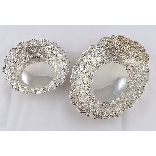 19 - A late Victorian oval silver dish having repousse decoration; a similar circular dish.  Oval dish 26...