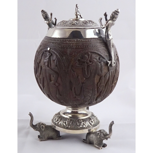 21 - A carved coconut covered pot having white metal handles, mounts and circular stand supported by thre...