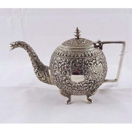 22 - A teapot having raised and chased decoration, Anglo-Thai / Siam white metal, approximately 200mm han...