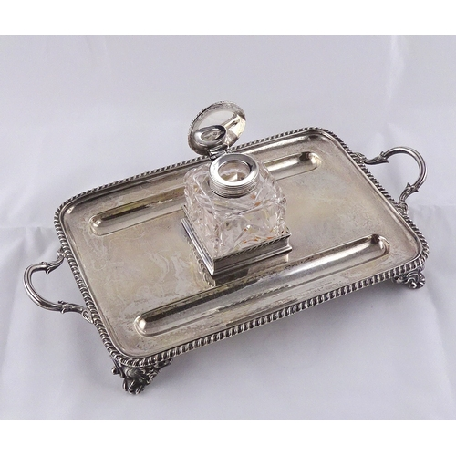 24 - A silver desk stand, with central glass and silver inkwell, London 1901.  294mm handle to handle / s...