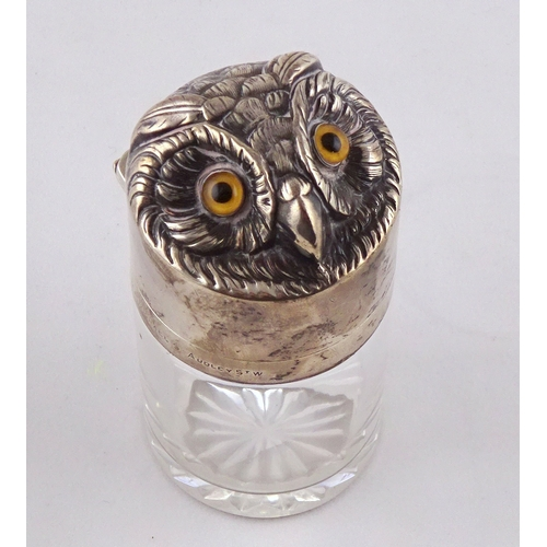 44 - A glass salts bottle having a hinged silver lid styled as an owl's head, inner glass stopper lacking...
