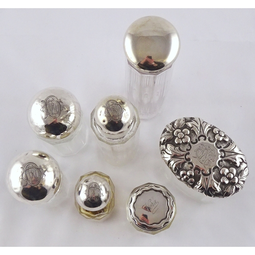 45 - Seven various silver topped glass dressing set flasks.  Tallest 185mm (by instruction of the family ...