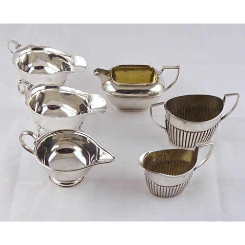 52 - A pair of silver sauce boats,143mm long; another silver sauce boat having presentation inscription; ...