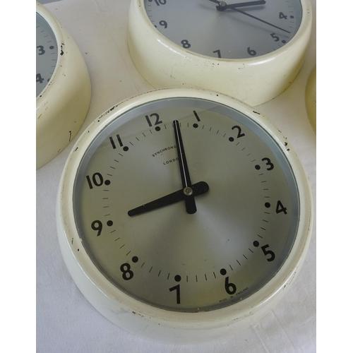 33 - Four mid century electric clocks 26cm diameter.