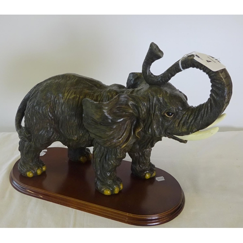 4 - A resin figure of an elephant on a wooden plinth 36cm wide 30 cm high.