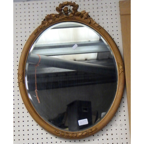 21 - A large oak framed mirror87 x 70cm together with an oval bevelled mirror 60cm long (2).