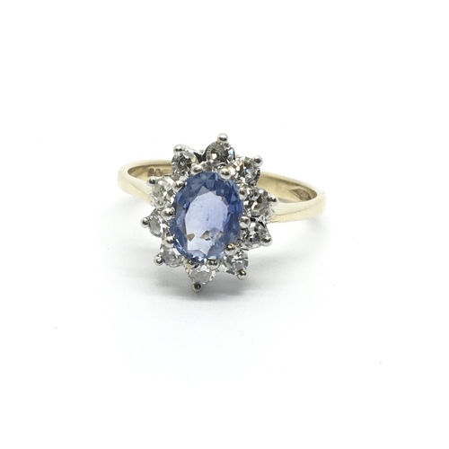 10 - A 9ct gold ring set with a central sapphire and surrounded by ten diamonds, approx 1/2ct, approx 2.2...