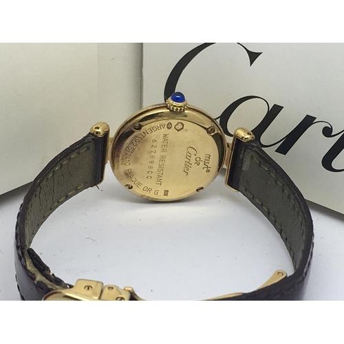 2 - A Silver gilt Must De Cartier ladies wristwatch, serial no. 62789800, with Original booklet and matc...