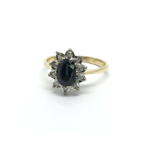 33 - An 18ct gold ring set with a central sapphire and surrounded by diamonds, approx 3.2g and approx siz...