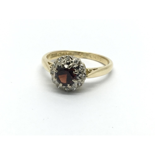 41 - An 18ct gold ring set with a central garnet and surrounded by diamonds, approx 3.3g and approx size ...