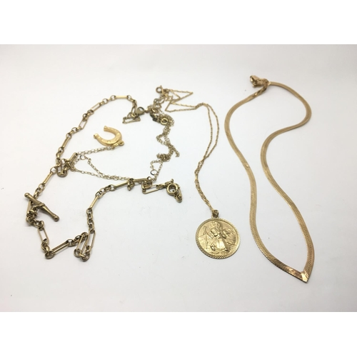27 - A gold necklace with a horseshoe pendant, a St Christopher pendant on chain and a wishbone necklace ...