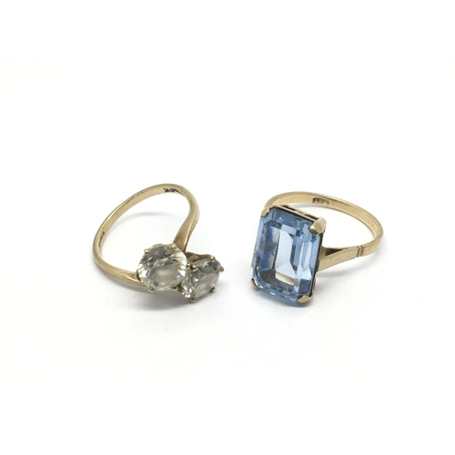 46 - A 9ct gold ring inset with an aquamarine coloured stone and one other 9ct gold crossover ring set wi...