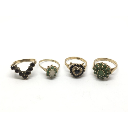 54 - Four gold rings inset with garnet and emerald, approx 10.5g....