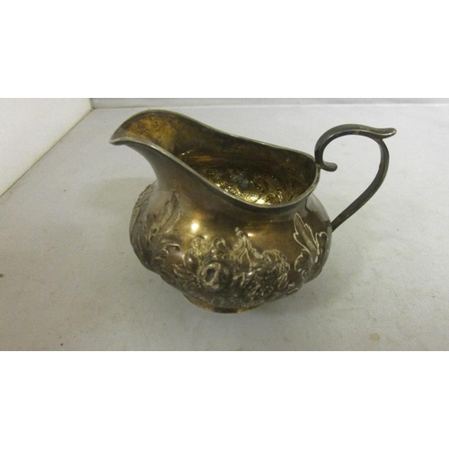 57 - Solid silver cream jug with embossed floral decoration London 1828 makers mark rubbed 132 g...