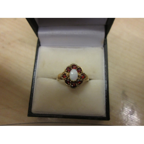 59 - 9 ct gold ring set with garnet surrounding a single opal size 54, 2.8 g...