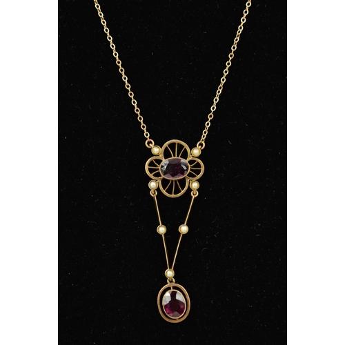 31 - AN EARLY 20TH CENTURY GOLD GEM PENDANT designed as an oval garnet within an open flower shape surrou...