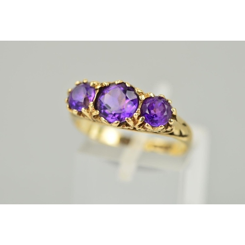 37 - A MID TO LATE 20TH CENTURY THREE STONE AMETHYST RING, scroll detail to shoulders and sides, ring siz...