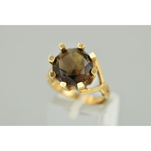 40 - A 9CT GOLD SMOKY QUARTZ RING, the circular smoky quartz within a thick eight claw setting with a rin...