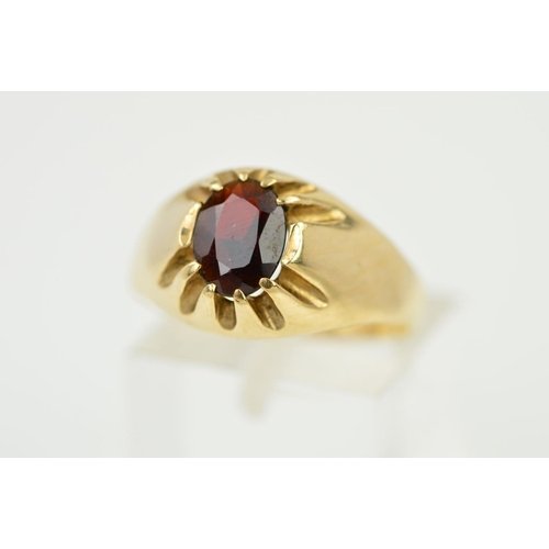 52 - A 9CT GOLD RED PASTE SIGNET RING designed with an oval red paste within a claw setting to the tapere...