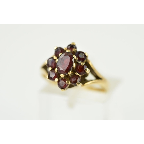 53 - A 9CT GOLD GARNET CLUSTER RING, the central oval garnet within a circular garnet surround to the bif...
