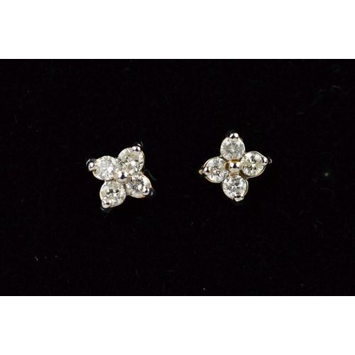 54 - A PAIR OF 9CT GOLD DIAMOND EAR STUDS, each designed as four brilliant cut diamonds in a floral desig...