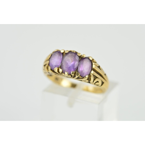22 - A LATE 20TH CENTURY 9CT GOLD THREE STONE AMETHYST RING, scroll engraved sides and shoulders, rings s...