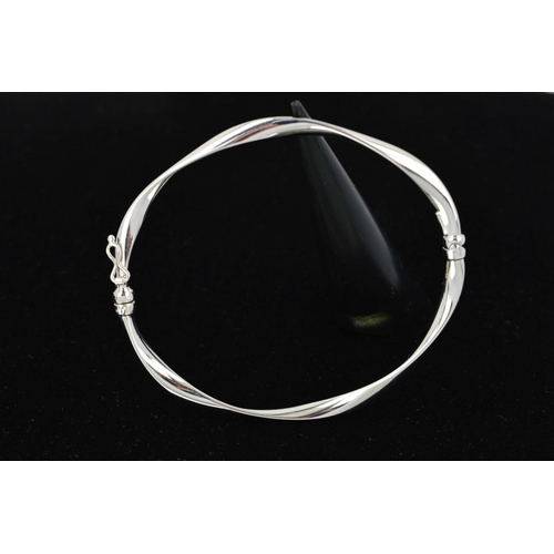 41 - A 9CT WHITE GOLD HINGED BANGLE, the twisted design with a sprung hinge and figure of eight clasp, wi...