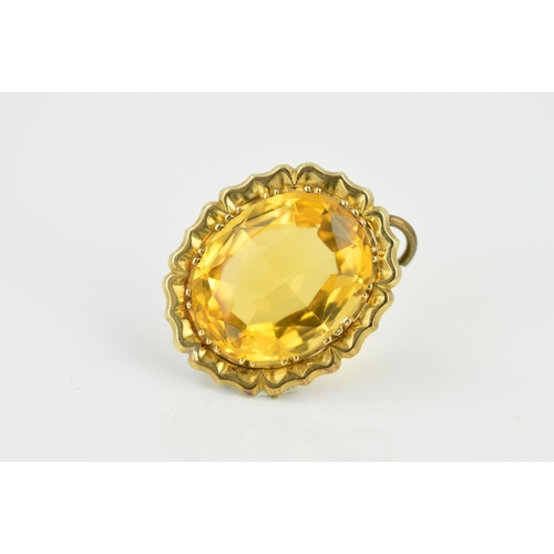 42 - AN EARLY 20TH CENTURY CITRINE PENDANT, the oval faceted citrine within a flower shaped surround, len...