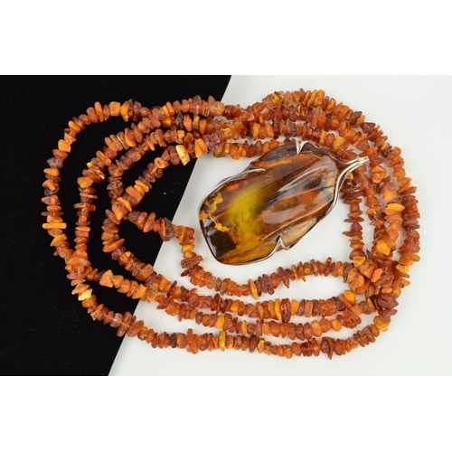 45 - AN AMBER NECKLACE AND PENDANT, the pendant designed as a large polished piece of amber within an abs...