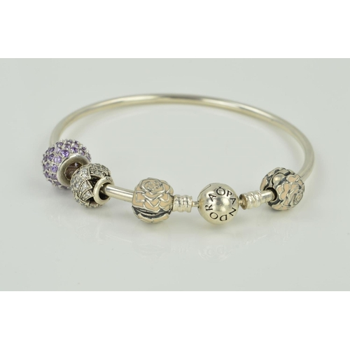 13 - A PANDORA CHARM BANGLE, the circular bangle with Pandora clasp, one non Pandora purple paste charm, ...