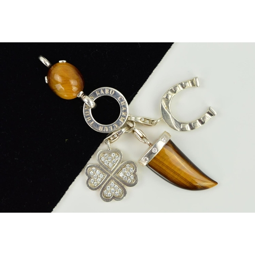 16 - FOUR THOMAS SABO CHARMS AND A CHARM CARRIER, to include two tiger's eye charms, a quatrefoil cubic z...