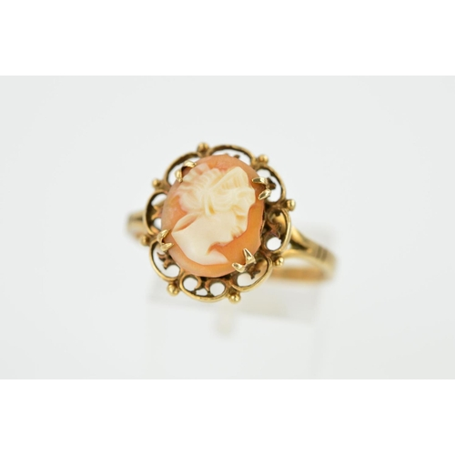 2 - A 9CT GOLD CAMEO RING, the central oval cameo panel depicting a lady in profile, within a scrolling ...