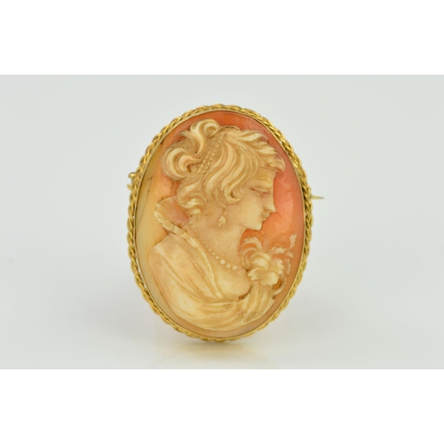 21 - A 9CT GOLD CAMEO BROOCH, of oval outline depicting a lady in profile to the double rope twist surrou...