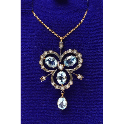 28 - A TOPAZ AND DIAMOND PENDANT NECKLACE, designed as a trefoil of three oval blue topaz gems within an ...