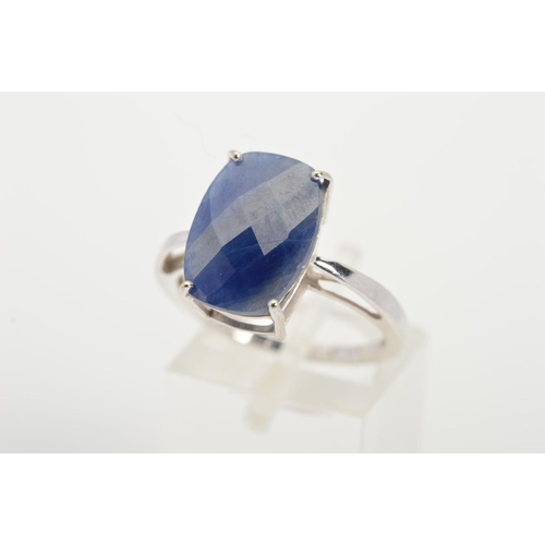 11 - A 9CT WHITE GOLD SAPPHIRE RING, designed as a curved rectangular sapphire within a four claw setting...