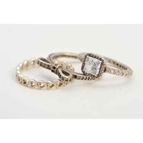 26 - THREE PANDORA RINGS, the first designed as a row of open heart shapes, the second a bow set with col...