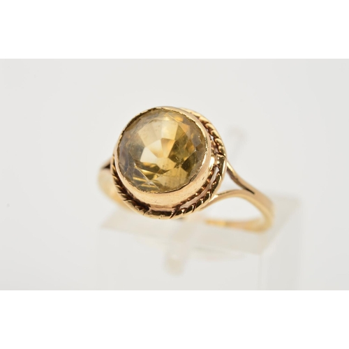 30 - A CITRINE RING, the circular citrine within a collet setting to the rope twist surround and bifurcat...