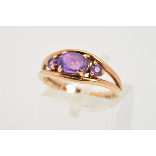 31 - A 9CT GOLD AMETHYST RING, designed as a central oval amethyst flanked by circular amethysts to the b...