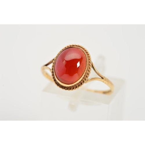 32 - A 9CT GOLD GEM RING, designed as a central oval red gem cabochon within a collet setting and rope tw...