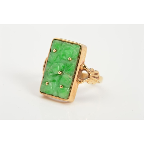 33 - A 9CT GOLD JADE RING, designed as a rectangular carved jade panel within a collet setting to the bif...